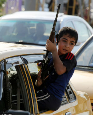 An Iraqi child who has joined the volunteer Shiite militias which are springing up to battle the Sunni Muslim group ISIS.