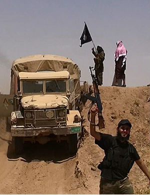 An image made available by the jihadist Twitter account Al-Baraka news on June 11, 2014 allegedly shows militants of the jihadist group Islamic State of Iraq and the Levant (ISIL) waving the Islamic Jihad flag and holding up their weapons as a vehicle drives on a newly cut road through the Syrian-Iraqi border between the Iraqi Nineveh province and the Syrian town of Al-Hasakah.
