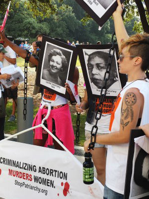 Abortion rights activists protest on August 4, 2014, outside a U.S. federal court in Austin, Texas, where a hearing started for a case by the Center for Reproductive Rights against a new set of restrictions on abortion clinics in the state that go into effect in September