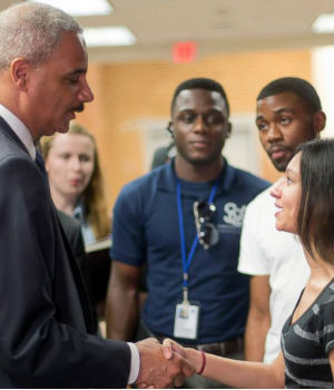 Attorney General Eric Holder shakes hands with Bri Ehsan, right, following his meeting with students at St. Louis Community College Florissant Valley.