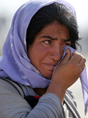 A Yazidi woman cries in a refugee camp where most of her surviving people now live.