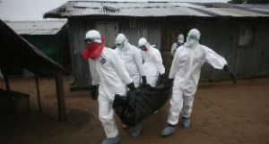 Aid workers carry the body of an Ebola victim, more than 1,000 have died of the virus.