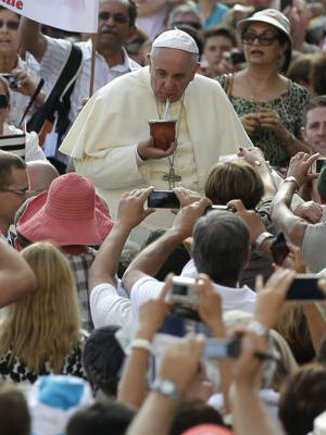 Pope Francis drinks a traditional South American drink called mate offered by the faithful as he arrives to lead his weekly audience in Saint Peter's Square.