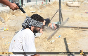A victim of ISIS kneels for a photograph and waits for the bullet that will end his life.