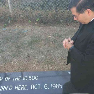 Fr. Pavone prays at the graveside of the children