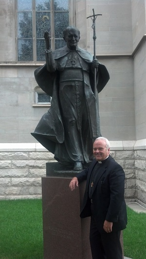 Deacon Keith Fournier standing under the beautiful bronze statue of John Paul II in Denver, Colorado.