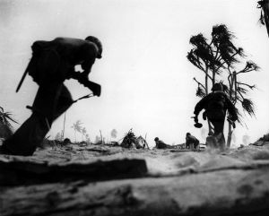 U.S. Marines advance while under fire from Japanese defensive positions.