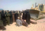 Image of Coptic monks lie before bulldozers as workers chant