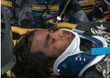 Image of A large crowd erupted in cheers as Pemba Tamang was carried out on a stretcher from the scene of the Kathmandu collapse. Wearing a blue shirt and a blue neck brace, Pemba was covered by dust, looking stunned.