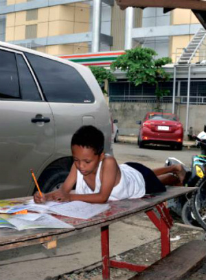 Inspiring story of a homeless nine-year-old Filipino boy who does his homework on the streets