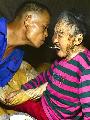 Chinese man without arms tends to paralyzed mother - feeding her food with spoon in teeth