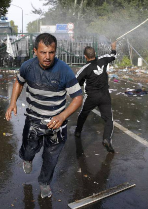 Hungarian police drive migrants away with tear gas and water cannons