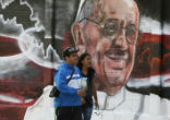 Image of Gang graffiti has been painted over with cheerful murals on the outskirts of Mexico City in time for the papal visit. Photo by EFE.