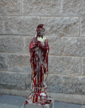 Satanists desecrate a statue of the Virgin Mary.