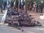 Image of Boko Haram soldiers hovering over innocents whom they slaughterd in the name of their