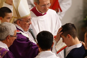 Pope Francis conferring the Sacrament of Confirmation on a young man.