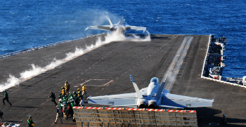 F-18 jets fly from the deck of the USS Carl Vinson.