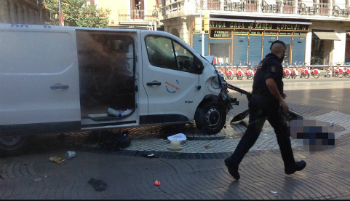 An officer walks past the van used in the attack.