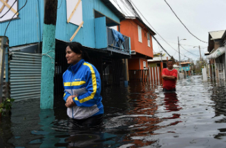 People walk though flooded streets in the aftermath of Maria. Several places remain flooded.