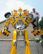 Image of Wang Liansheng stands on his 16-foot-tall model of autobot Bumblebee.