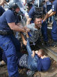 Image of Photos show a father trying to protect his wife and child by lying down on the tracks in protest. Hungarian officers dragged them away for their own safety.