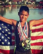 Image of Michael Riley Jr., three-time Junior Olympic qualifier posing with his medals.
