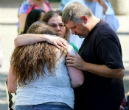 Image of Survivors embrace and pray in the aftermath of the shooting which left 9 people and the shooter dead.