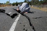 Image of A road worker examines damage done by a quake in California.