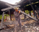 Image of A man removes a charred cross from a burned out church. Christian persecution takes place constantly around the world.