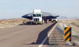 Image of A truck transports a mysterious, covered object to Area 51 under tight security.