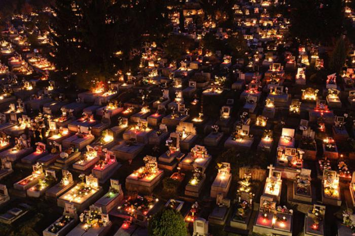 candles burning on a grave in hungary to mark all saints day