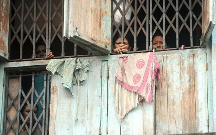 Indian sex workers peer out from a brothel in Mumbai.