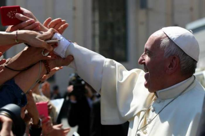 Pope Francis hands rosaries to pilgrims in St. Peter's Square.