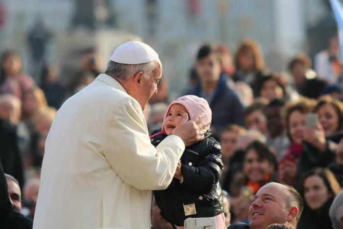 Pope Francis kisses a child in St. Peter's Square for the general audience.