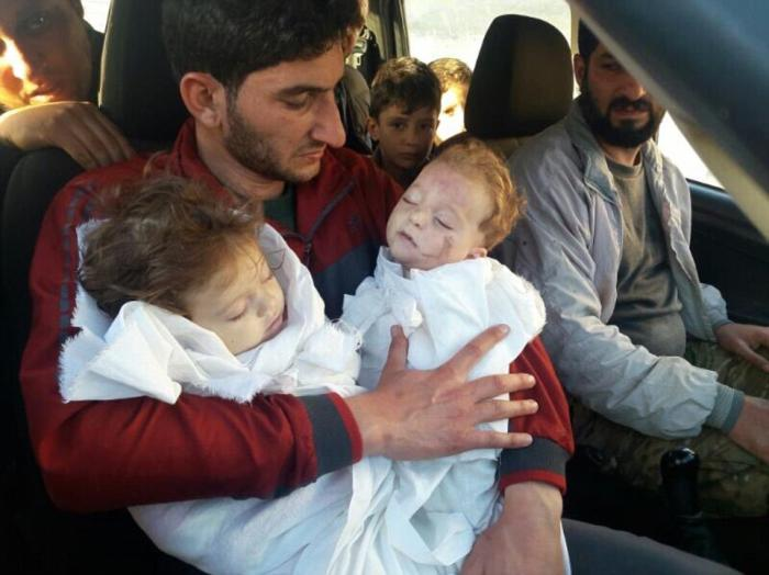 A father holds the bodies of his two children killed in the gas attack.