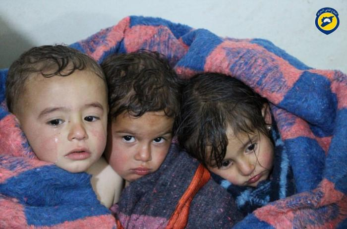 Child survivors are kept warm following the attacks.