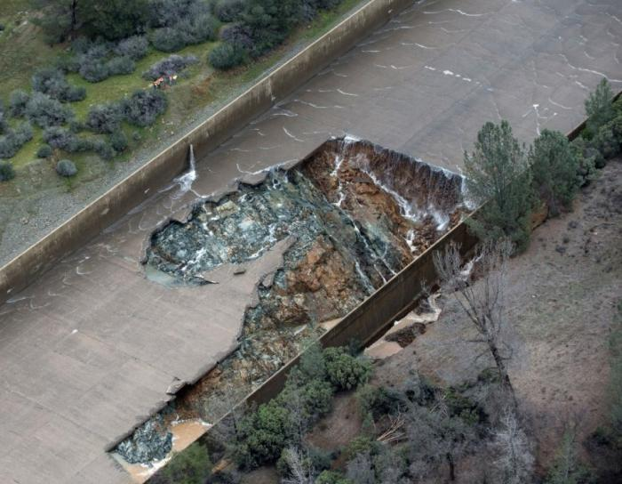 "Fig 9. Original ""Blow-out"" failure of Main Spillway. No ""Large Blocks"" present. The upper failure seam in the spillway is where seepage has been observed originating in the spillway during non-operating conditions (dry - See Fig 14). This seam is also where multiple repairs have been performed over the years as evidenced in images of ""cuts"" in the slab concrete for nearly the full length of this seam. After additional flows of 30,000 cfs to 33,000 cfs on Feb 8, 2017, and then 45,000 cfs on Feb 9, 2017, is when rapid upslope spillway backcutting collapsing failure progressed. This ""rapid upslope"" spillway collapse was most likely accelerated by the unstable large ""void fill"" blocks that had little to no anchor bar integrity remaining. The spillway flow was stopped on Feb 10, 2017 for an inspection (See Fig 8.). That is when the stack of ""large slab blocks"" were observed washed to the far side of the erosion channel, abutting the still intact broken upper part of the lower spillway. This is the critical evidence that the ""large slab blocks"" originated just above this ""original blow-out failure"" location & in the same large highly erodible weathered rock seam (Fig 8.)."
