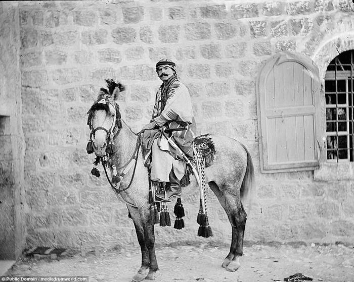 A Bedouin man sits on an elaborately saddled horse in Jerusalem.