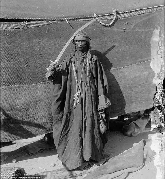 A Bedouin man poses with his sword. Despite the weapon, Bedouins generally lead a peaceful existence, traveling raising animals, and trading as they go.