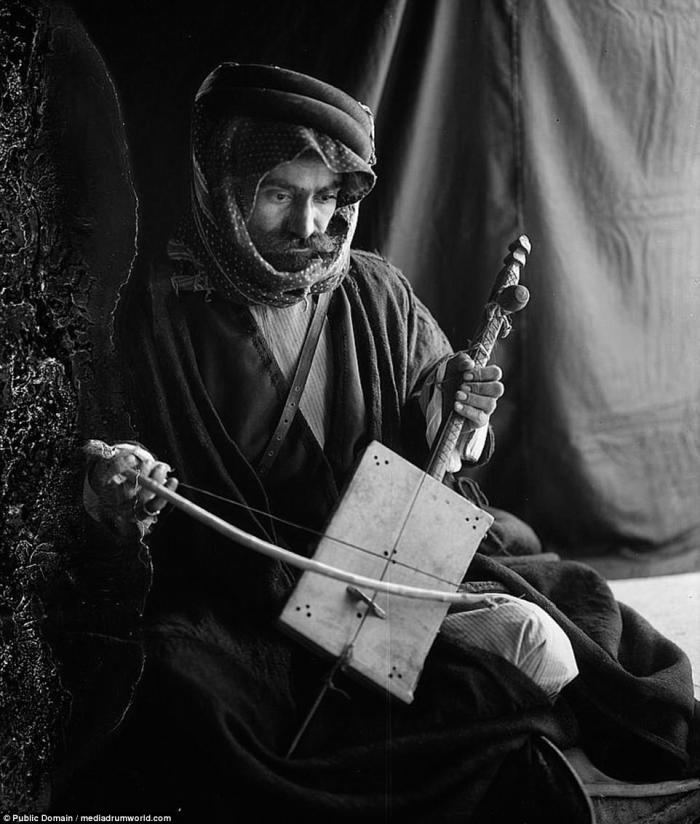 A Bedouin man poses with a traditional musical instrument.