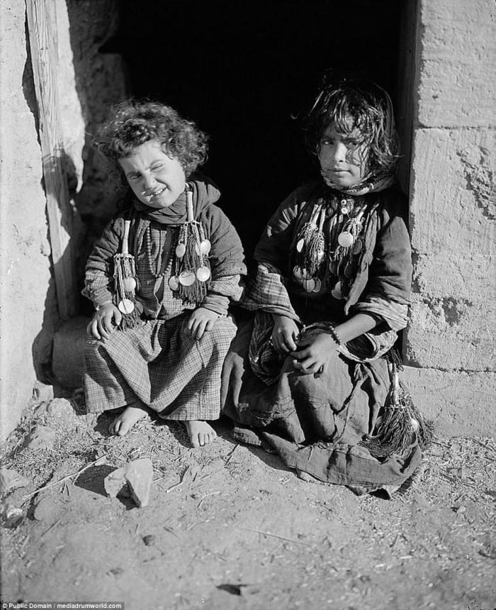 Bedouin children in traditional dress sit in a doorway for a picture.
