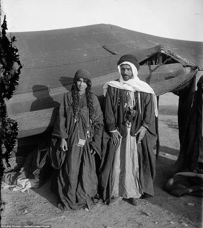 A Bedouin man and his wife pose in front of their tent. Today, Bedouin tents contain a few more modern luxuries. In some places, tourists can spend the night in such tents.