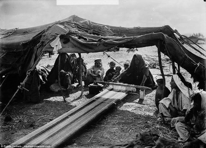 A Bedouin woman weaves under a tent.