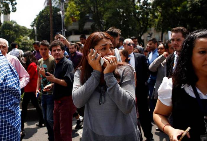 An emotional woman speaks on a cellphone in the aftermath of the quake. Earlier in the day, the city held earthquake drills on the anniversary of the 1985 quake which killed thousands.