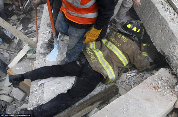 A firefighter works to rescue a person trapped under the debris of a collapsed building.