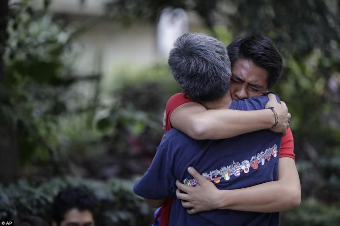A pair of relatives embrace after finding one another unhurt. This was the most common scene in the city, but the focus remains on locating trapped survivors.