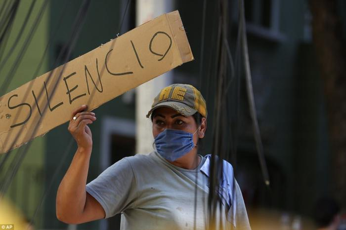 A worker holds up a sign calling for silence. Workers periodically asked the crowds to be silent so they could listen for the cries of people trapped in the rubble.