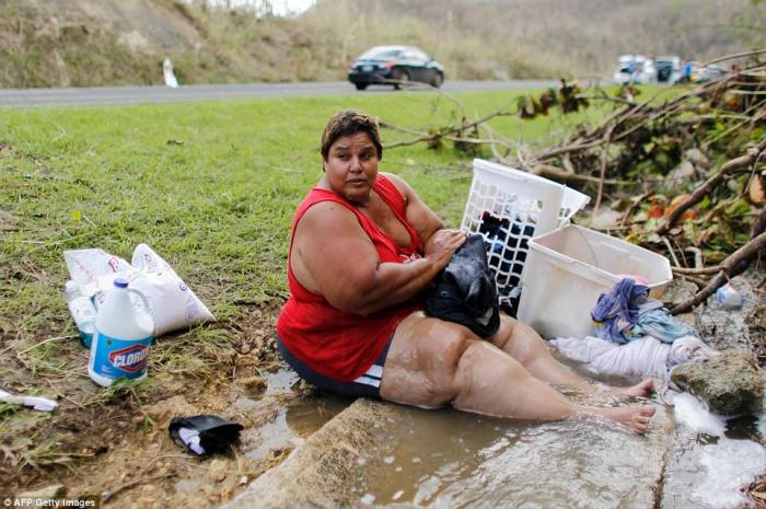 A woman does laundry in a flooded gutter. The island remains without water.