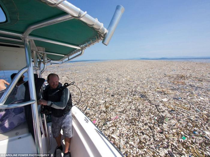 A diver looks with concern at the patch of plastic surrounding his boat. Imagine planning a vacation getaway only to see it turn into a dump.