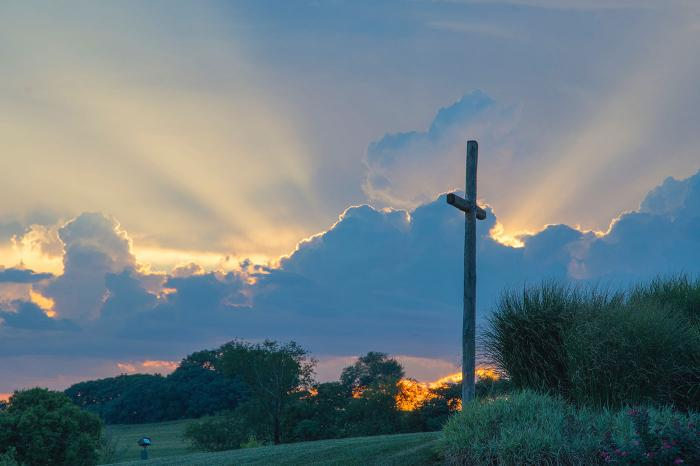 Cross on a hill side with light shining through the clouds